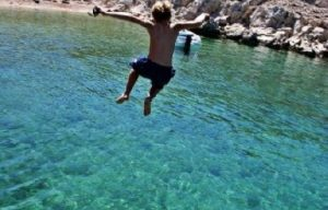 Child jumping in the crystal clear sea of Pag Island